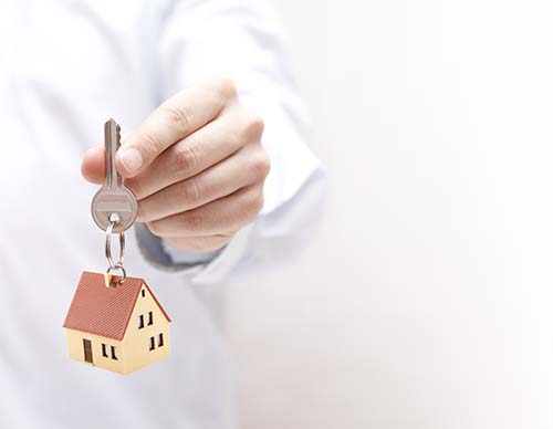man holding a house key with a keyring of a house on it