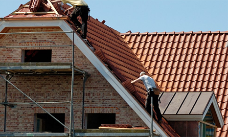 two men on top of a house roof fixing slates